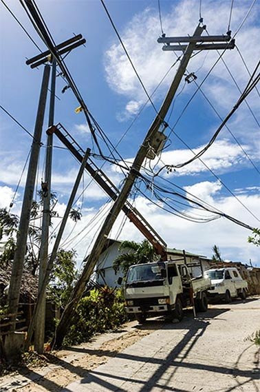 Coffman supplies disaster relief equipment to help communities restore their power supply. A collection of downed utility poles after a storm, with a service crane attempting to fix a power line.